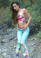 Long haired brunette posing and stripping outdoors