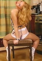 Cute blond teen doing a striptease in the kitchen