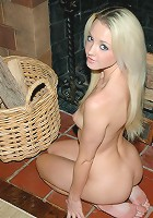 Sweet Kelly sits by the fireplace naked.