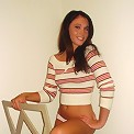 Abby straddles a chair as she strips